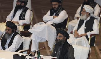 Taliban co-founder Mullah Abdul Ghani Baradar speaks, bottom right, talks at the opening session of the peace talks between the Afghan government and the Taliban in Doha, Qatar, Saturday, Sept. 12, 2020. (AP Photo/Hussein Sayed)