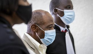 """Paul Rusesabagina, center, who inspired the film """"Hotel Rwanda"""" for saving people from genocide, appears at the Kicukiro Primary Court in the capital Kigali, Rwanda Monday, Sept. 14, 2020. Rusesabagina became famous for protecting more than 1,000 people as a hotel manager during Rwanda's 1994 genocide and was awarded the U.S. Presidential Medal of Freedom in 2005 but Rwandan authorities accused him of supporting the armed wing of his opposition political platform, which has claimed responsibility for deadly attacks inside Rwanda. (AP Photo)"""
