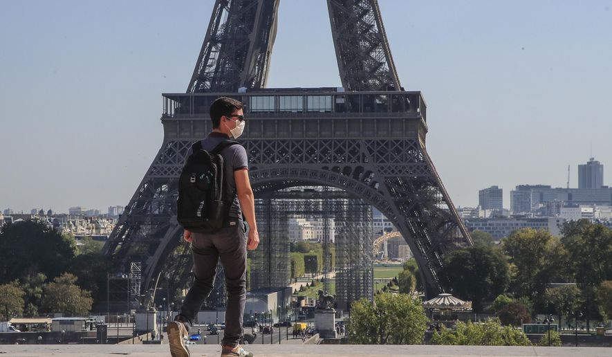 A man wearing protective a face mask as a precaution against the coronavirus walk at Trocadero plaza near Eiffel Tower in Paris, Monday, Sept. 14, 2020. France sees a substantial increase in Covid-19 cases. (AP Photo/Michel Euler) ** FILE **