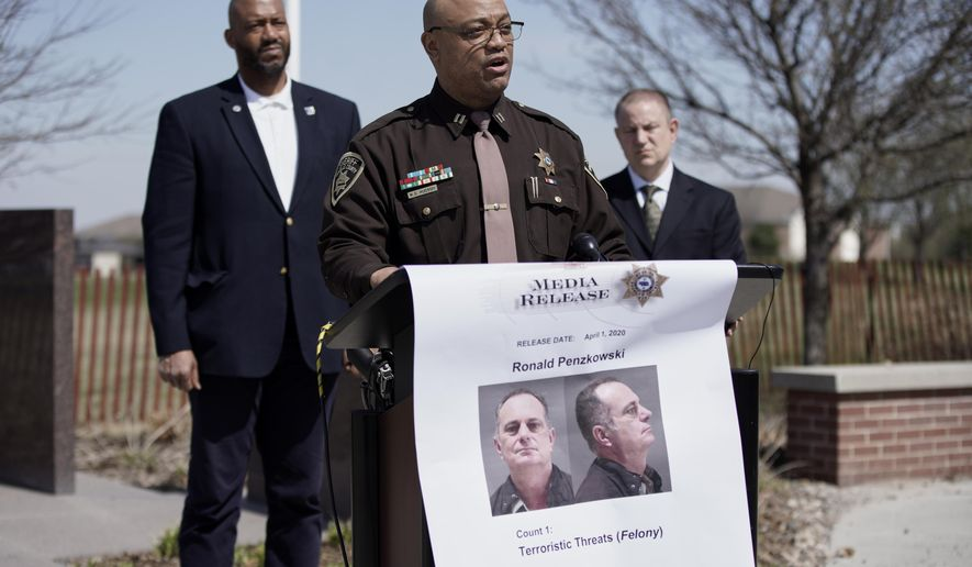 "Capt. Wayne Hudson of the Douglas County Sheriff's office speaks at a news conference in Omaha, Neb., Wednesday, April 1, 2020, to announce that Ronald Penzkowski a former director of communications for then-Omaha Mayor Jim Suttle a decade ago, was arrested on suspicion of making terroristic threats and stalking. Investigators say that Penzkowski sent at least 15 email messages to Dr. Adi Pour, Douglas County Health Director, threatening to ""lynch"" her and to cut her throat. The emails made reference to public health measures, such as stay-at-home orders intended to slow the spread of the coronavirus. (AP Photo/Nati Harnik)"