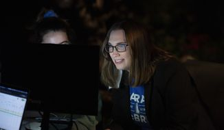 Transgender activist Sarah McBride, who hopes to win in the primary for the Delaware Senate, watches a computer screen at her watch party in Wilmington, Del., Tuesday, Sept. 15, 2020. (AP Photo/Jason Minto)