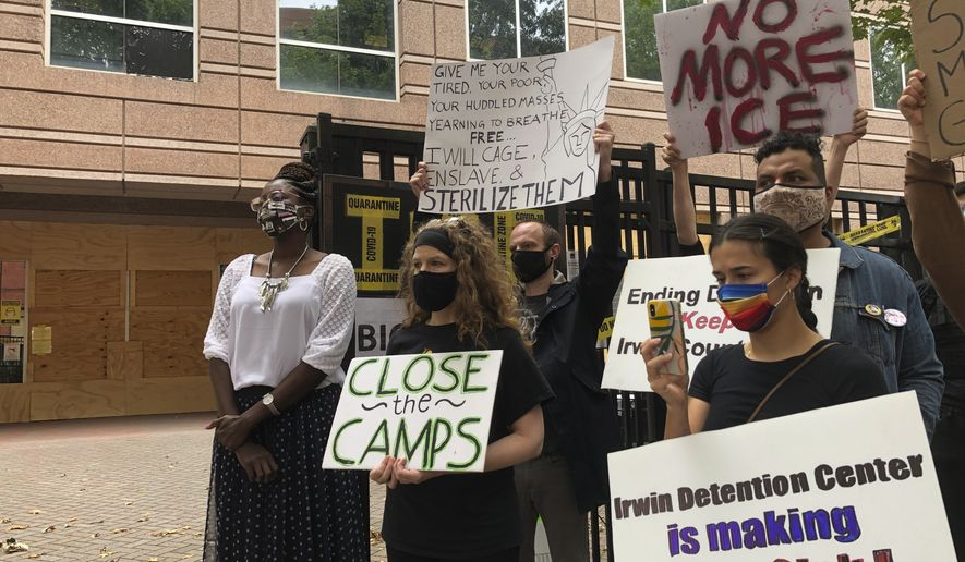 Dawn Wooten, left, a nurse at Irwin County Detention Center in Ocilla, Georgia, listens to a speaker at a Tuesday, Sept. 15, 2020 news conference in Atlanta protesting conditions at the immigration jail. Wooten says authorities denied COVID-19 tests to immigrants, performed questionable hysterectomies and shredded records in a complaint filed to the inspector general of the U.S. Department of Homeland Security. (AP Photo/Jeff Amy)