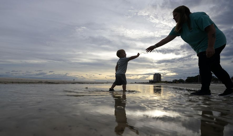 Nikita Pero of Gulfport, Miss., walks with her son Vinny Pero, 2, on the beach along the Gulf of Mexico in Biloxi, Miss., Monday, Sept. 14, 2020. Hurricane Sally is expected to make landfall along the Gulf Coast sometime through the night and morning. (AP Photo/Gerald Herbert)