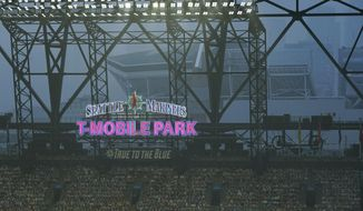 Smoke from wildfires fills the air at T-Mobile Park as photos of fans are displayed in the left field bleachers and CenturyLink Field is visible behind the ballpark sign during the second baseball game of a doubleheader between the Seattle Mariners and the Oakland Athletics, Monday, Sept. 14, 2020, in Seattle. (AP Photo/Ted S. Warren)