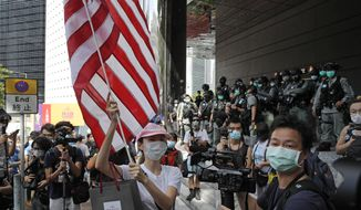 """In this July 4, 2020, file photo, a woman carries an American flag during a protest outside the U.S. Consulate in Hong Kong. The U.S. has issued a new advisory Tuesday, Sept. 15, 2020, warning against travel to mainland China and Hong Kong, citing the risk of """"arbitrary detention"""" and """"arbitrary enforcement of local laws."""" (AP Photo/Kin Cheung, File)"""