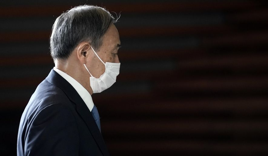 Former Chief Cabinet Secretary Yoshihide Suga walks at the prime minister's office after a cabinet meeting Wednesday, Sept. 16, 2020, in Tokyo. Prime Minister Shinzo Abe and his Cabinet resigned, clearing the way for his successor Suga to take over after parliamentary confirmation later in the day. (AP Photo/Eugene Hoshiko)