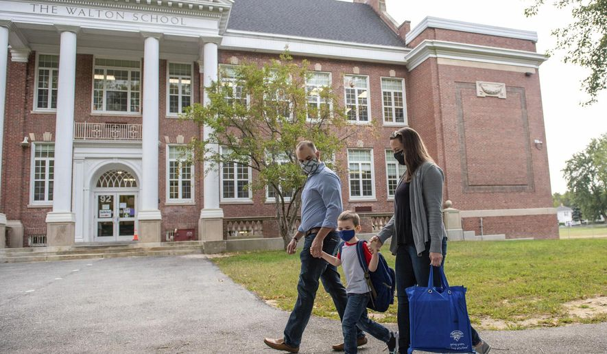Andrea and Doug Tomer, walk their son Landon to school at the Walton School on Monday morning, Sept. 14, 2020 for the first day of school.  (Andree Kehn/Sun Journal via AP)