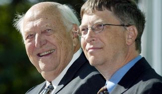 In this Sept. 12, 2003, file photo, William H. Gates Sr., left, smiles while sitting next to his son, Bill Gates Jr., during the dedication and grand opening of the William H. Gates Hall, the new home of the University of Washington School of Law in Seattle. Bill Gates Sr., a lawyer and philanthropist and father of Microsoft co-founder Bill Gates, died Monday, Sept. 14, 2020, at age 94. (AP Photo/John Froschauer, File)