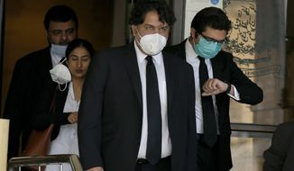 Faisal Siddiqi, center, a lawyer for the family of Daniel Pearl, an American Wall Street Journal reporter who was kidnapped and killed in Pakistan, leaves the Supreme Court after an appeal hearing in the Pearl case, in Islamabad, Pakistan, Tuesday, Sept. 15, 2020. The much-awaited court hearing against the acquittal of a British Pakistani man and three others in the 2002 kidnapping and killing of Pearl, was delayed for a week on Tuesday when judges could not take up the case due to the absence of a prosecutor whose mother died recently, a defense lawyer said. (AP Photo/Anjum Naveed)