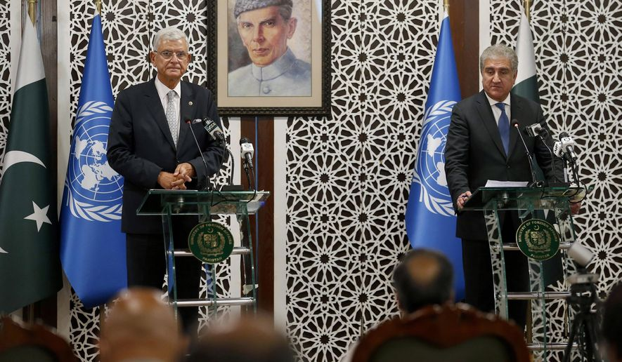 United Nations General Assembly President-elect Volkan Bozkir, left, and Pakistan Foreign Minister Shah Mahmood Qureshi give a joint press conference in Islamabad, Pakistan, Monday, Aug. 10, 2020. Bozkir arrived in Islamabad on a two-day visit. Portrait in background show Muhammad Ali Jinnah, founder of Pakistan. (AP Photo/Anjum Naveed)
