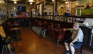 Joe Bastone, owner of Yankee Tavern, sits in an empty dining room before the Boston Red Sox played the New York Yankees on Friday, Aug. 14, 2020, in New York. The coronavirus pandemic has been especially hard on businesses that rely on ballpark traffic, eliminating crowds at major league games, and leading to rules that limit the amount of people they can have inside their doors at the same time. (AP Photo/Frank Franklin II)