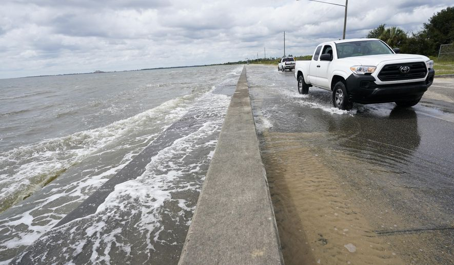 Waters from the Guld of Mexico poor onto a local road, Monday, Sept. 14, 2020, in Waveland, Miss. Hurricane Sally, one of a record-tying five storms churning simultaneously in the Atlantic, closed in on the Gulf Coast on Monday with rapidly strengthening winds of at least 100 mph (161 kph) and the potential for up to 2 feet (0.6 meters) of rain that could bring severe flooding. (AP Photo/Gerald Herbrt)