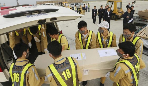 FILE - In this Nov. 27, 2019, file photo, airport personnel load a coffin into an ambulance at the Noi Bai airport in Hanoi, Vietnam. A court in central Vietnam has sentenced seven people for smuggling a woman who later died in a truck together with 38 other people as they were being transported into Britain. (Vietnam News Agency via AP, File)