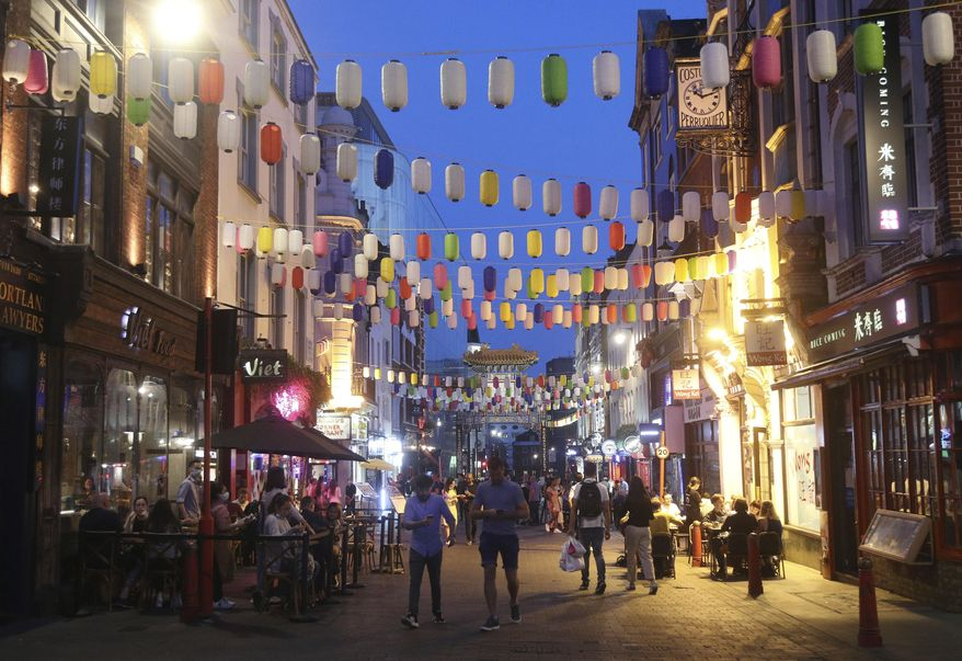 People drink and dine out in Chinatown, London, Monday Sept. 14, 2020. New rules preventing gatherings of more than six people go into effect in England, Scotland and Wales on Monday, in an effort to simplify directives meant to prevent the spread of COVID-19. (Yui Mok/PA via AP)