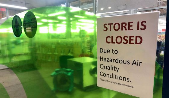 A sign at a Whole Foods in Lake Oswego, Ore., advises that the store is closed due to poor air quality Monday, Sept. 14, 2020. Another sign said all Whole Foods stores in the Portland Metro area will be closed at least through Thursday due to air quality. People across the West struggled under acrid-yellowish green smog from raging wildfires that seeped into homes and businesses, sneaked into cars through air conditioning vents and caused the temporary closure of iconic locations such as Powell's Books and the Oregon Zoo. (AP Photo/Gillian Flaccus) ** FILE **