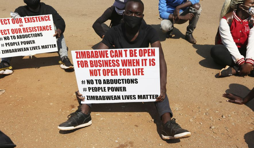 A student and human rights activist holds a banner during a peaceful protest in Harare, Monday, Sept. 14, 2020. Human rights defenders say it appears the government is using restrictions imposed to combat COVID-19 to suppress political criticism. Opposition officials, human rights groups and some analysts accuse Mnangagwa of abusing the rights of critics, using tactics as harsh as his predecessor, the late Robert Mugabe. (AP Photo/Tsvangirayi Mukwazhi)