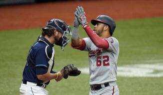 Washington Nationals' Luis Garcia (62) celebrates his two-run home run off Tampa Bay Rays relief pitcher Nick Anderson during the 10th inning of a baseball game Wednesday, Sept. 16, 2020, in St. Petersburg, Fla. Catching for the Rays is Kevan Smith. (AP Photo/Chris O'Meara)