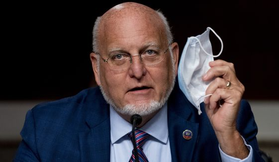 """Centers for Disease Control and Prevention Director Dr. Robert Redfield holds up his mask as he speaks at a Senate Appropriations subcommittee hearing on a """"Review of Coronavirus Response Efforts"""" on Capitol Hill, Wednesday, Sept. 16, 2020, in Washington. (AP Photo/Andrew Harnik, Pool)"""