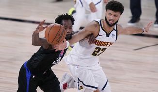 Los Angeles Clippers guard Patrick Beverley (21) is pressured by Denver Nuggets guard Jamal Murray (27) as he drives with the ball during the second half of an NBA conference semifinal playoff basketball game Tuesday, Sept. 15, 2020, in Lake Buena Vista, Fla. (AP Photo/Mark J. Terrill)
