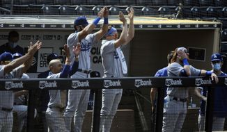 The Los Angeles Dodgers bench claps for Will Smith after he hit a two-run double against the San Diego Padres in the fifth inning of a baseball game Wednesday, Sept. 16, 2020, in San Diego. (AP Photo/Derrick Tuskan)