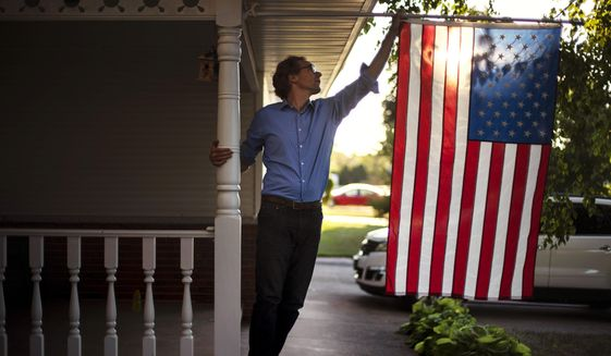 Outagamie County Executive Tom Nelson adjusts the American flag hanging off his front porch in Appleton, Wis., Aug. 18, 2020. (AP Photo/David Goldman/File)
