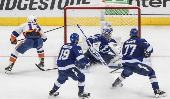 Tampa Bay Lightning goaltender Andrei Vasilevskiy (88) makes a save on New York Islanders center Mathew Barzal (13) during overtime in Game 5 of the NHL hockey Eastern Conference final, Tuesday, Sept. 15, 2020, in Edmonton, Alberta. (Jason Franson/The Canadian Press via AP)
