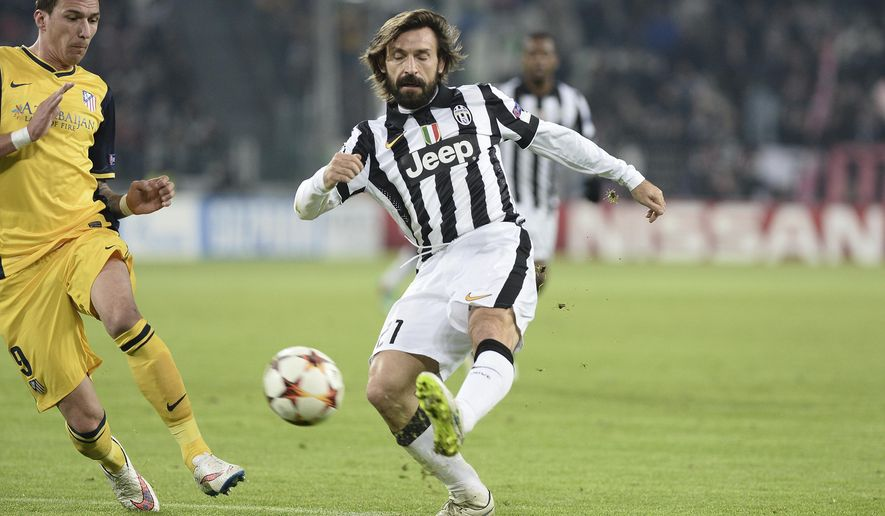 FILE - In this Dec. 9, 2014 file photo, Juventus' Andrea Pirlo, right, challenges the ball with Atletico' Mario Mandzukic during a Champions League, Group A, soccer match between Juventus and Atletico de Madrid at the Juventus stadium in Turin, Italy. New Juventus coach Andrea Pirlo had his coaching qualification rubber-stamped by the Italian soccer federation on Wednesday, Sept. 16, 2020. (AP Photo/Massimo Pinca, file)