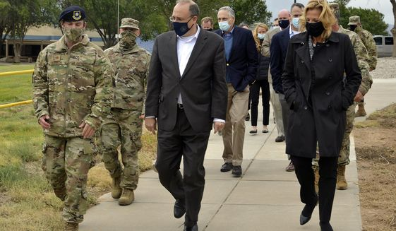 In this Sept. 9, 2020, image provided by the U.S. Air Force, is Marshall Billingslea, special presidential envoy for arms control, center, and National Nuclear Security Administration Administrator Lisa Gordon-Hagerty, right, walking with Air Force personnel between meetings at Kirtland Air Force Base in Albuquerque, N.M.  The Trump administration has sketched out a framework that it hopes will avoid a three-way arms race as a deadline nears for extending the only remaining nuclear arms control deal with Russia and as China looks to expand its nuclear forces.  (Todd R. Berenger/U.S. Air Force, via AP)