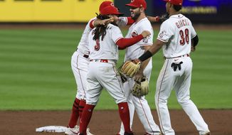 Cincinnati Reds' Joey Votto, back left, Freddy Galvis, second from left, Mike Moustakas, middle, and Jose Garcia celebrate after the Reds defeated the Pittsburgh Pirates 1-0 in a baseball game Wednesday, Sept. 16, 2020, in Cincinnati. (AP Photo/Aaron Doster)