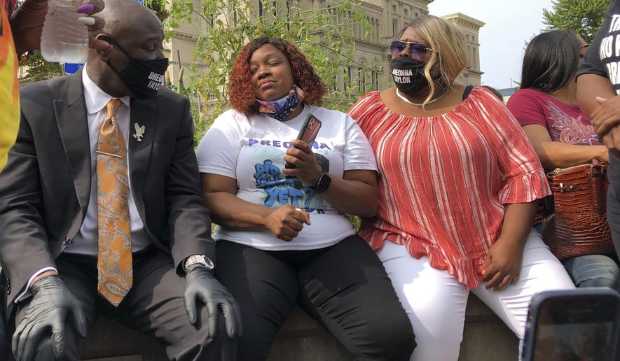 Tamika Palmer, Breonna Taylor's mother, in white beside Attorney Ben Crump, left, speak in Louisville, Ky., after settlement was announced. The city of Louisville will pay $12 million to the family of Breonna Taylor and reform police practices as part of a lawsuit settlement months after Taylor's slaying by police thrust the Black woman's name to the forefront of a national reckoning on race, Mayor Greg Fischer announced Tuesday.(AP Photo/Dylan Lovan)
