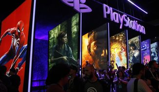 FILE - In this June 14, 2018, file people stand online next to the PlayStation booth at the 24th Electronic Entertainment Expo E3 at the Los Angeles Convention Center. Sony said Wednesday, Sept. 16, 2020 its upcoming PlayStation 5 video game console will cost $500 and launch Nov. 12, setting up a holiday battle with Microsoft's Xbox Series X over whose new console will turn up more under the tree this year. (AP Photo/Damian Dovarganes, File)
