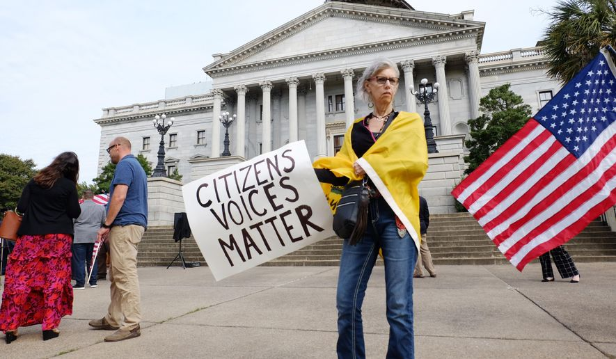 Kim Rulf, of Greenville, South Carolina, attends a protest on the South Carolina Statehouse grounds in Columbia, S.C., Tuesday, Sept. 15, 2020, calling for Gov. Henry McMaster to end the state of emergency issued for the coronavirus pandemic and for lawmakers to remove mask mandates across the state. About 50 people gathered without wearing masks at the Capitol building on the morning the state legislature was set to begin a two-week special session. (AP Photo/Michelle Liu) **FILE**