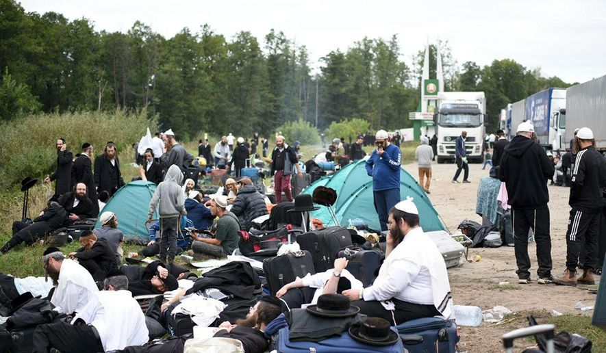 Jewish pilgrims sit on the Belarus-Ukraine border, in Belarus, Tuesday, Sept. 15, 2020. About 700 Jewish pilgrims are stuck on Belarus' border due to coroavirus restrictions that bar them from entering Ukraine. Thousands of pilgrims visit the city each September for Rosh Hashana, the Jewish new year. However, Ukraine closed its borders in late August amid a surge in COVID-19 infections. (TUT.by via AP)