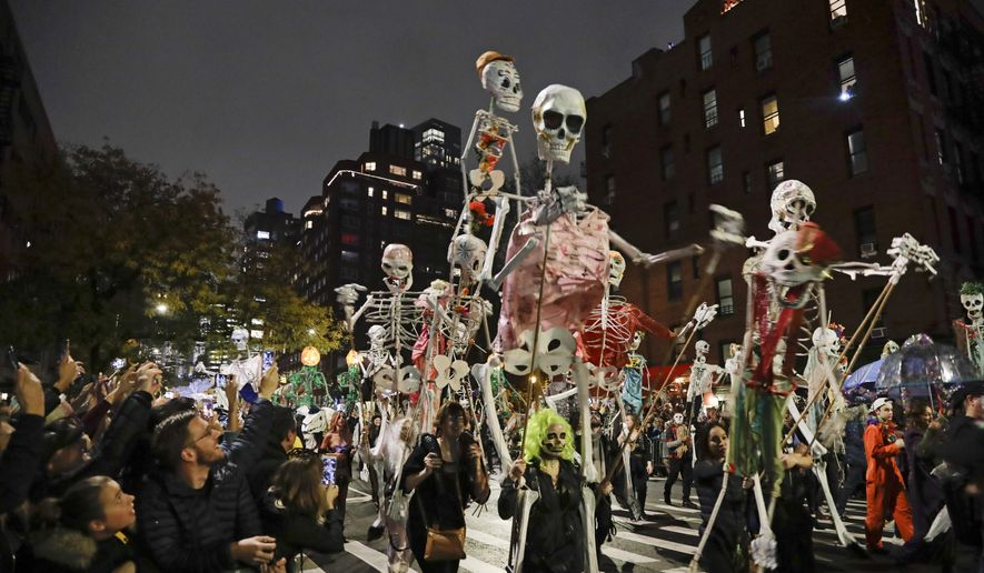 FILE - Revelers march during the Greenwich Village Halloween Parade in New York on Oct. 31, 2019. The holiday so many look forward to each year is going to look different in the pandemic as parents and the people who provide Halloween fun navigate a myriad of restrictions and safety concerns. (AP Photo/Frank Franklin II, File)
