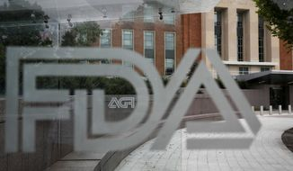 This Aug. 2, 2018, file photo shows the U.S. Food and Drug Administration building behind FDA logos at a bus stop on the agency's campus in Silver Spring, Md. (AP Photo/Jacquelyn Martin, File)