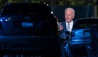 Audience members watch from their cars as Democratic presidential candidate former Vice President Joe Biden, seen on a large monitor, speaks during a CNN town hall moderated by Anderson Cooper in Moosic, Pa., Thursday, Sept. 17, 2020. (AP Photo/Carolyn Kaster)