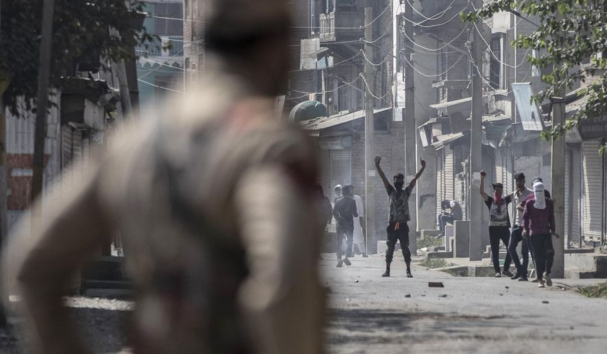 A Kashmiri man shouts freedom slogans as a police officer looks from a distance after a gun battle in Srinagar, Indian controlled Kashmir, Thursday, Sept. 17, 2020. The gunfight erupted shortly after scores of counterinsurgency police and soldiers launched an operation based on a tip about the presence of militants in a Srinagar neighborhood, Pankaj Singh, an Indian paramilitary spokesman, said. (AP Photo/Mukhtar Khan)