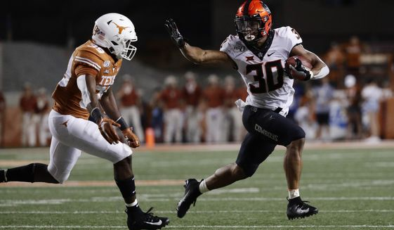 FILE - In this Sept. 21, 2019, file photo, Oklahoma State running back Chuba Hubbard (30) looks to fend off Texas defensive back Montrell Estell during the second half of an NCAA college football game in Austin, Texas. Oklahoma State plays Tulsa this week. The game was initially scheduled Sept. 12, but was postponed five days before that to allow the virus-affected Golden Hurricane more time to prepare for the season. (AP Photo/Eric Gay, File)