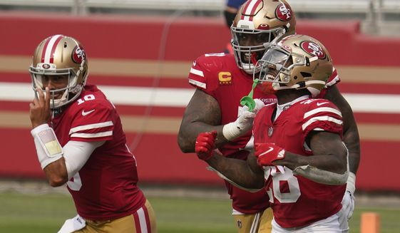 San Francisco 49ers running back Jerick McKinnon, right, celebrates with quarterback Jimmy Garoppolo, left, and offensive tackle Trent Williams after scoring a touchdown against the Arizona Cardinals during the second half of an NFL football game in Santa Clara, Calif., Sunday, Sept. 13, 2020. (AP Photo/Tony Avelar)