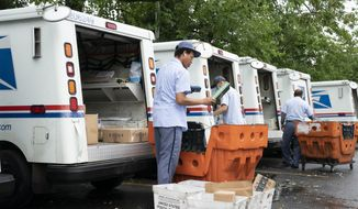 """FILE - In this July 31, 2020, file photo, letter carriers load mail trucks for deliveries at a U.S. Postal Service facility in McLean, Va. A U.S. judge on Thursday, Sept. 17, 2020, blocked controversial Postal Service changes that have slowed mail nationwide. The judge called them """"a politically motivated attack on the efficiency of the Postal Service"""" before the November election. (AP Photo/J. Scott Applewhite, File)"""