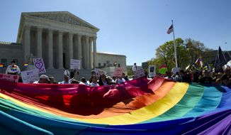 FILE - In this April 28, 2015 file photo, demonstrators stand in front of a rainbow flag of the Supreme Court in Washington. In 2019, there were slightly less than 1 million same-sex couple households in the U.S., and a majority of those couples were married. New figures released Thursday, Sept. 17, 2020 by the U.S. Census Bureau shows that of the 980,000 same-sex couple households, 58% were married couples and 42% were unmarried partners. (AP Photo/Jose Luis Magana, File)