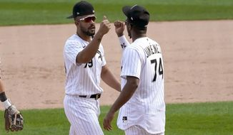 Chicago White Sox's Jose Abreu (79) and Eloy Jimenez celebrate the team's 4-3 win over the Minnesota Twins in  baseball game Thursday, Sept. 17, 2020, in Chicago. The White Sox clinched a playoff spot for the first time since 2008. (AP Photo/Charles Rex Arbogast)