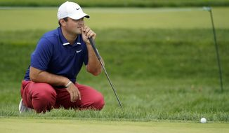 Patrick Reed, of the United States, checks his lie on the 17th green during the first round of the US Open Golf Championship, Thursday, Sept. 17, 2020, in Mamaroneck, N.Y. (AP Photo/Charles Krupa)