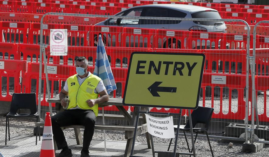 A staff member waits at the entrance to nearly empty lanes of a Covid-19 drive thru testing facility at Twickenham stadium in London, Thursday, Sept. 17, 2020.  Britain has imposed tougher restrictions on people and businesses in parts of northeastern England on Thursday as the nation attempts to stem the spread of COVID-19, although some testing facilities remain under-utilised. (AP Photo/Frank Augstein)
