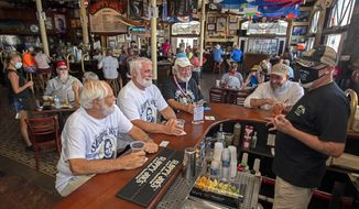 In this photo provided by the Florida Keys News Bureau, Ernest Hemingway look-alikes, including from left, Dusty Rhodes, Tim Stockwell and Charlie Boice chat with bartender Lou Gammel, right, at Sloppy Joe's, Thursday, Sept. 17, 2020, in Key West, Fla. The iconic Florida Keys bar reopened Thursday after being sidelined by the coronavirus pandemic, with the annual Hemingway Look-Alike Contest, that was to mark its 40th anniversary and take place in July, a highlight of Key West's Hemingway Days festival. Boice won the contest in 2015. (Rob O'Neal/Florida Keys News Bureau via AP)