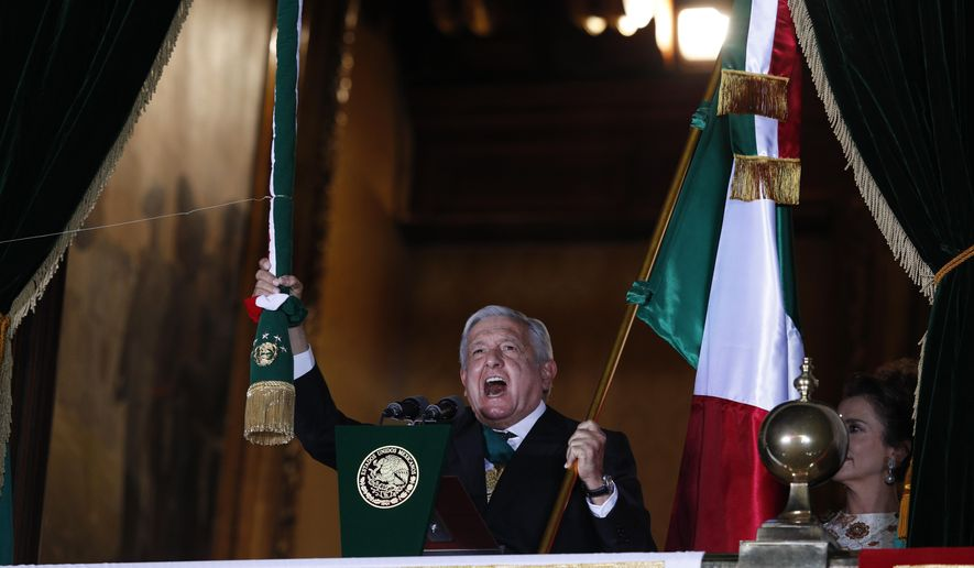 """Mexican President Andres Manuel Lopez Obrador rings the bell as he gives the annual independence shout from the balcony of the National Palace to kick off subdued Independence Day celebrations amid the ongoing coronavirus pandemic, at the Zocalo in Mexico City, Tuesday, Sept. 15, 2020. Instead of the throngs of supporters who pack the Zocalo in a typical year, this Independence Day the president faced an empty plaza as he gave the traditional """"Grito de Dolores,"""" which commemorates the 1810 call to arms by priest Miguel Hidalgo that began the struggle for independence from Spain. (AP Photo/Rebecca Blackwell)"""