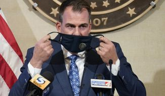 Oklahoma Gov. Kevin Stitt removes his mask before speaking at a news conference Thursday, Sept. 17, 2020, in Oklahoma City. Stitt said again that he will not issue a statewide mask mandate, despite a recommendation from the White House Coronavirus Task Force. (AP Photo/Sue Ogrocki)