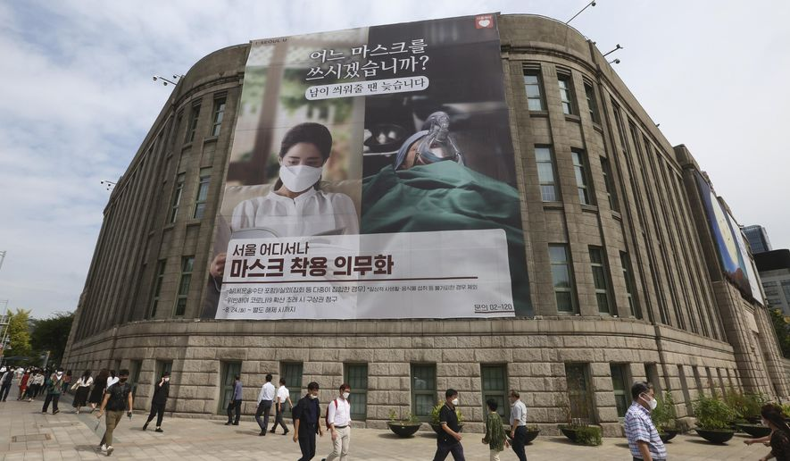 "People wearing face masks to help protect against the spread of the coronavirus walk under a banner informing mandatory mask wearing in front of Seoul City Hall in Seoul, South Korea, Thursday, Sept. 17, 2020. The banner reads: "" Which mask would you wear?"" (AP Photo/Ahn Young-joon)"