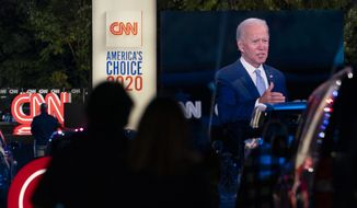 Audience members watch from their cars as Democratic presidential candidate Joe Biden, seen on a monitor, speaks during a CNN town hall in Moosic, Pa., Thursday, Sept. 17, 2020. (AP Photo/Carolyn Kaster)