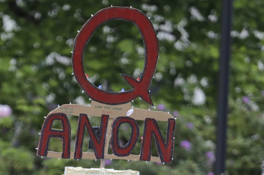 In this May 14, 2020 file photo, a person carries a sign supporting QAnon at a protest rally in Olympia, Wash. (AP Photo/Ted S. Warren, File)